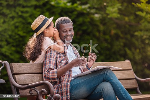 istock grandchild whispering to her smiling grandfather while sitting on bench in park 834348902