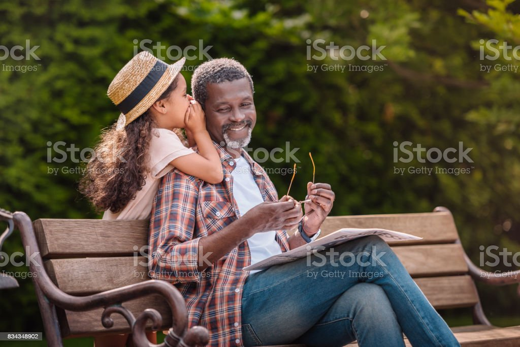 grandchild whispering to her smiling grandfather while sitting on bench in park stock photo