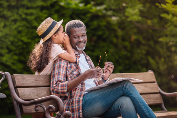 grandchild whispering to her smiling grandfather while sitting on bench in park - grandparents stock photos and pictures