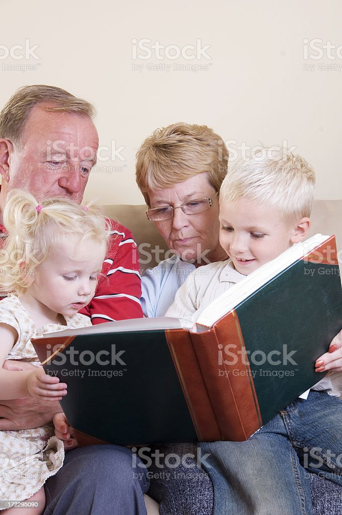 grandchildren and grandparents reading royalty-free stock photo