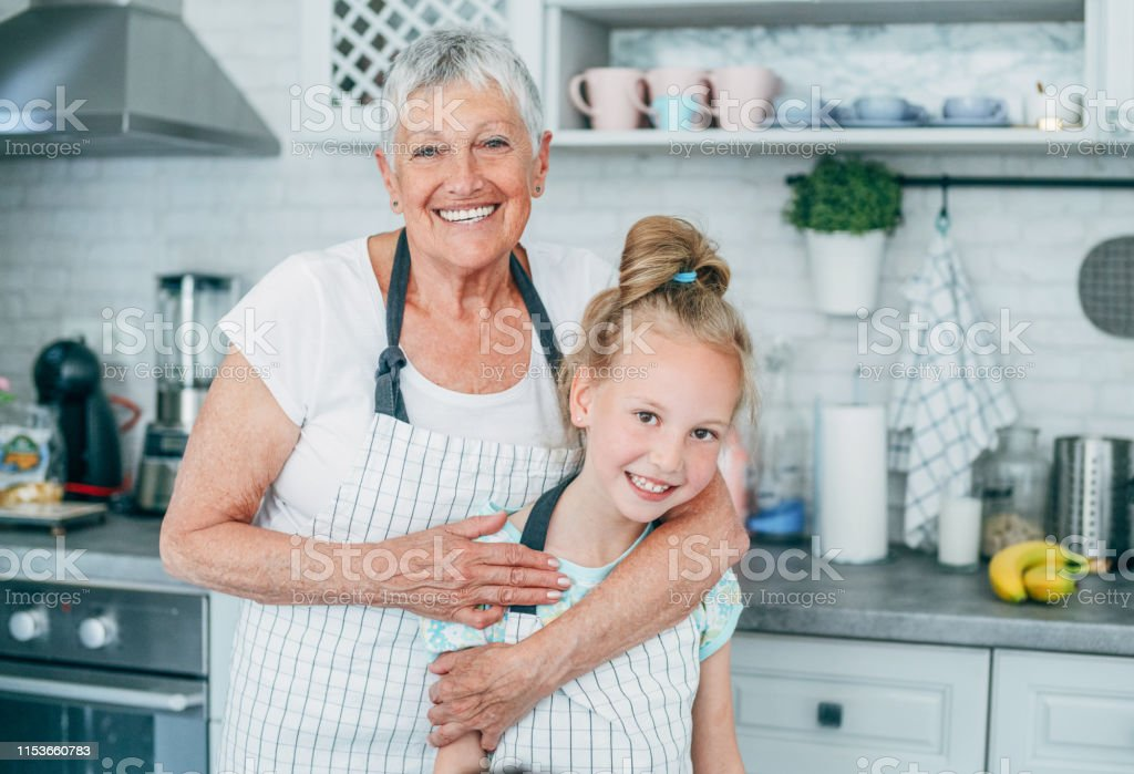 Beautiful grandmother embracing cute little granddaughter in the...