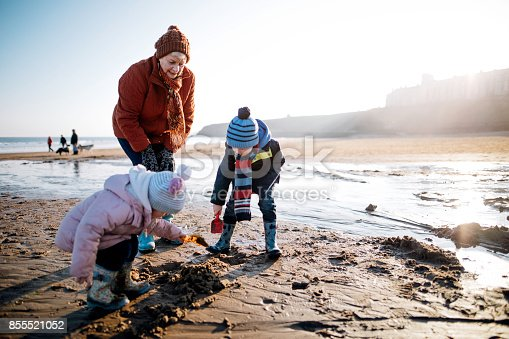 Grandmother with her grandchildren on the beach Its cold outside so they are wrapped up warm. The children are playing in the sand and the woman is supervising