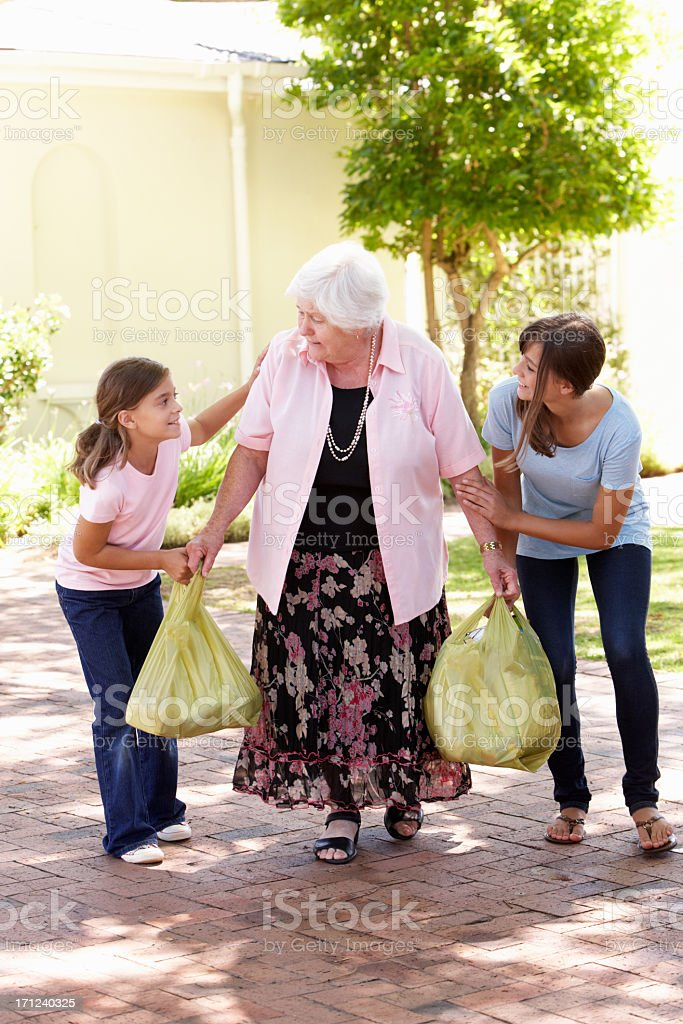 Grandchildren Helping Grandmother To Carry Shopping stock photo
