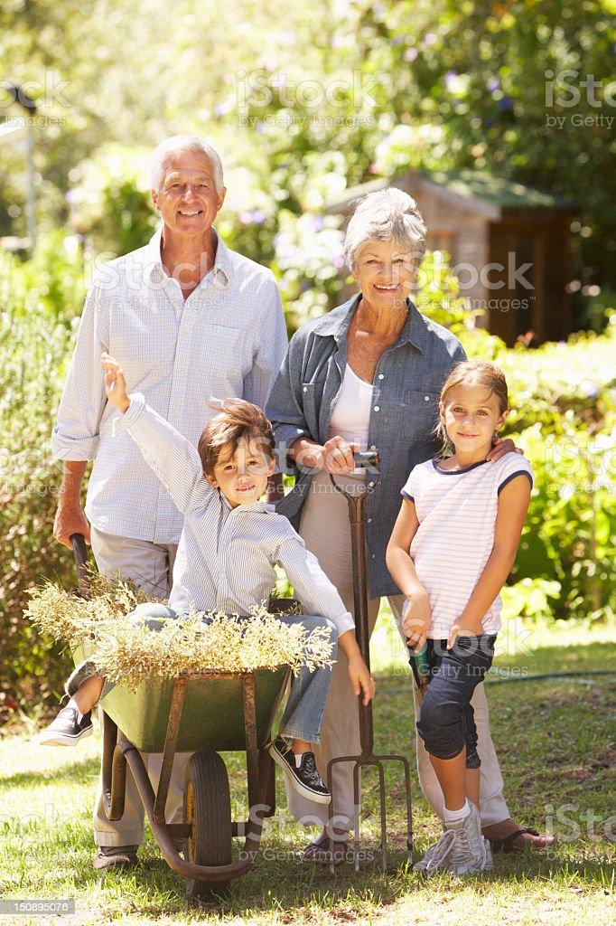 Grandchildren Helping Grandparents In Garden At Home Having Fun