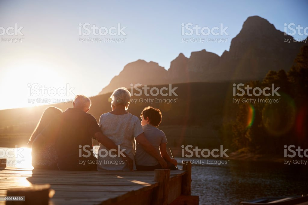 Grandchildren With Grandparents Sitting On Wooden Jetty By Lake stock photo