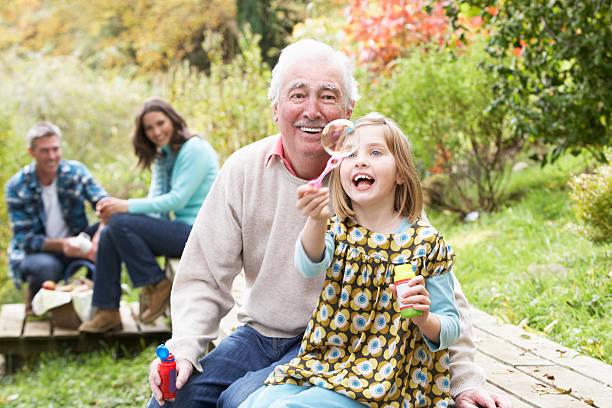 großvater und enkelin blasen blasen auf picknick mit der familie - kinder picknick spiele stock-fotos und bilder