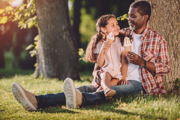 enkelin und großvater essen eis in den zapfen sitzen auf dem rasen - mensch isst gras stock-fotos und bilder