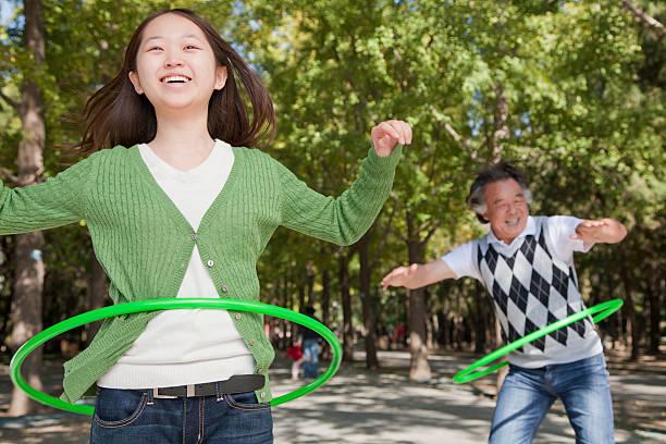 enkelin und großvater spielen mit kunststoff-hoop im park - hula hoop workout stock-fotos und bilder
