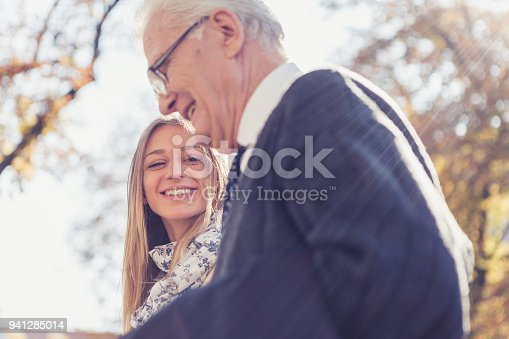 istock Granddaughter and grandfather walking in the park 941285014
