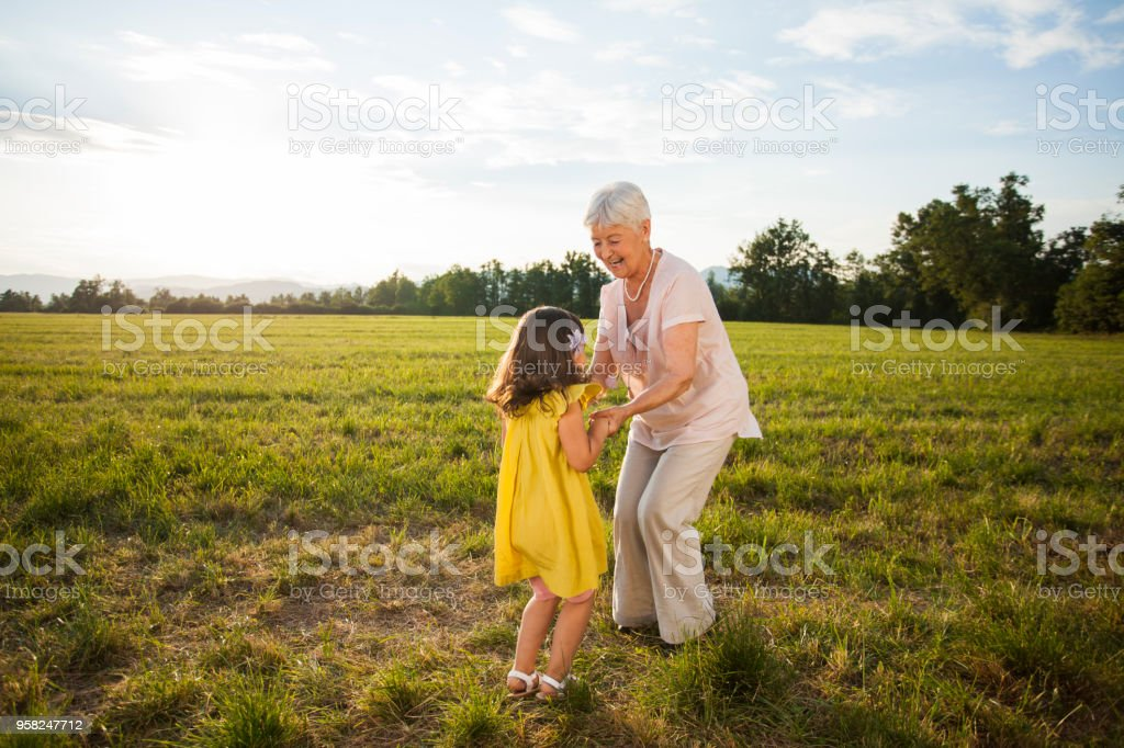 Granddaughter and grandmother dancing in nature Female senior adult holding hands with small girl, her grandchild and dancing in meadow. Nice sunny summer day. 6-7 Years Stock Photo
