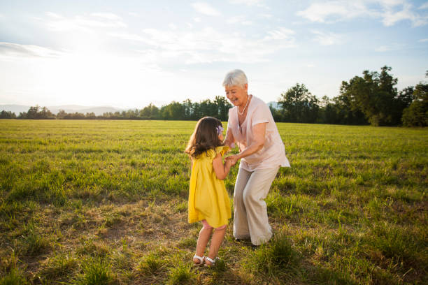 granddaughter and grandmother dancing in nature - granddaughter and grandmother stock photos and pictures