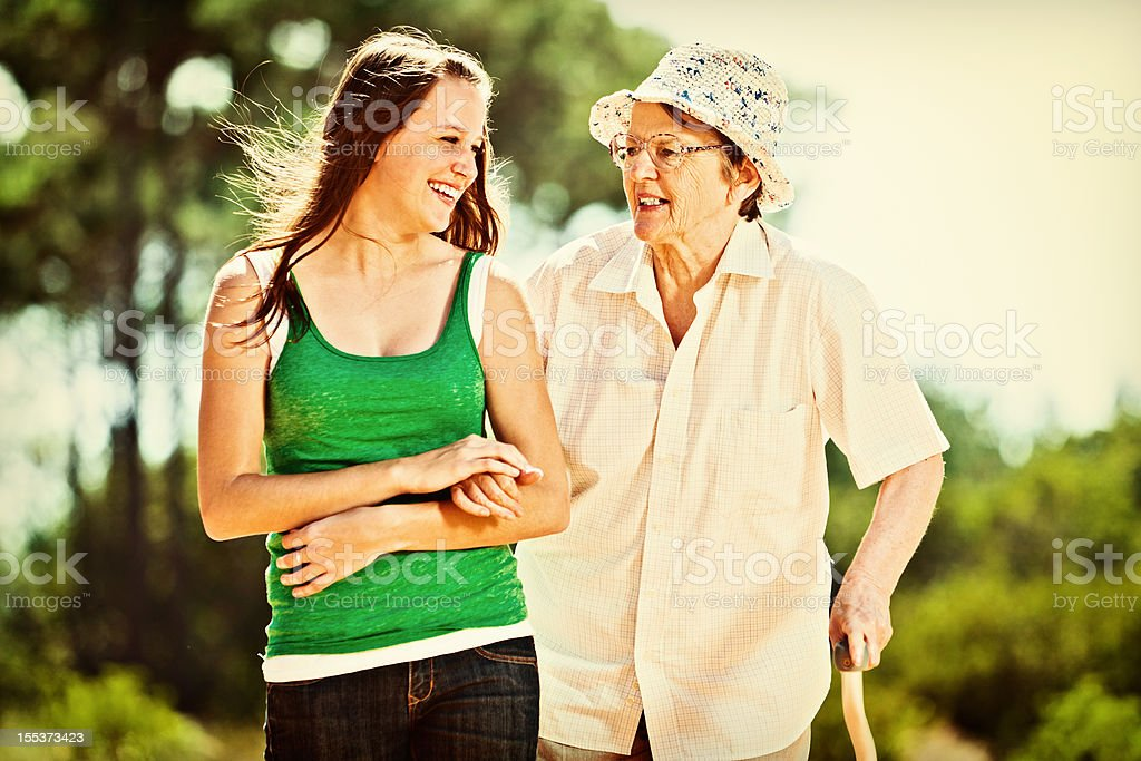 Granddaughter and grandmother smile as they go walking together royalty-free stock photo