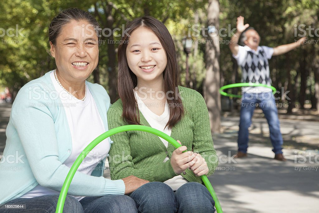 Granddaughter and grandparents playing with plastic hoop in the park royalty-free stock photo