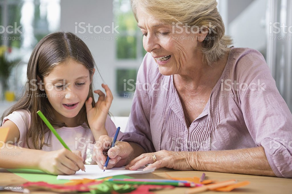 Granddaughter and her grandmother drawing royalty-free stock photo