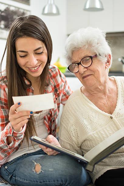 granddaughter and her grandmother sitting and looking at old photos. - senior fotoboek stockfoto's en -beelden