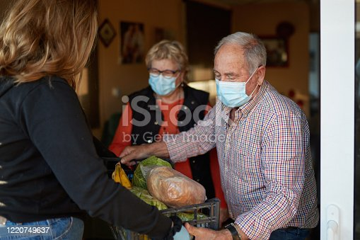 Senior couple on their 70s wearing a protective face mask picking up the shopping box that granddaughter is delivering in times of COVID-19, she is wearing mask and gloves.