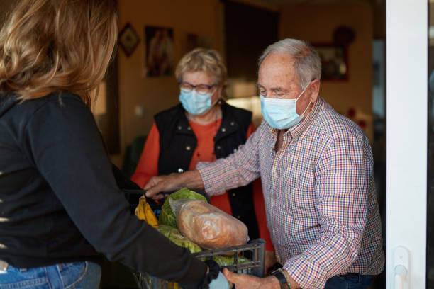 Granddaughter bringing the shopping to grandparents during pandemic at their home stock photo