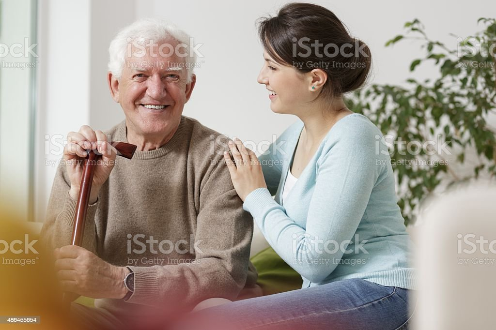Granddaughter caring about her grandfather stock photo