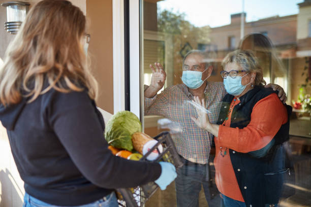 granddaughter delivers groceries to grandparents during pandemic - charity and relief work stock pictures, royalty-free photos & images
