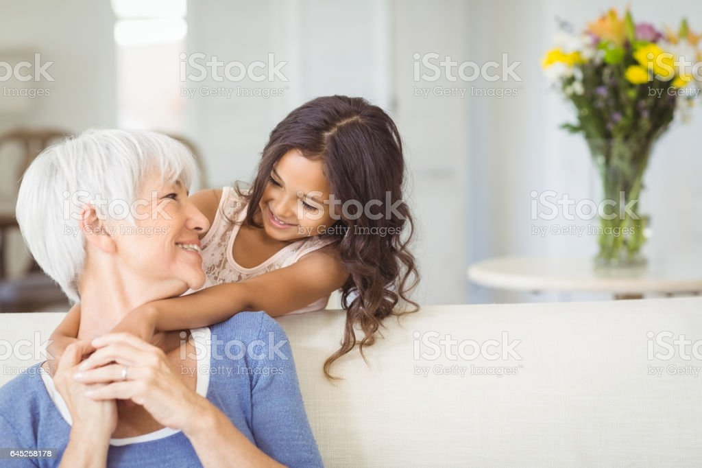 Granddaughter embracing her grandmother in living room royalty-free stock photo