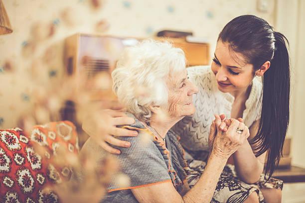 Enkelin umarmen Ihr glückliche Großmutter wie zu Hause fühlen. – Foto