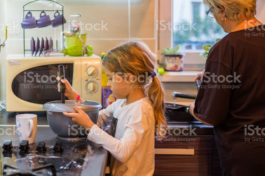 Granddaughter helping her granny in kitchen stock photo