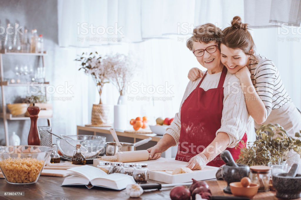 Granddaughter hugging grandmother in the kitchen stock photo