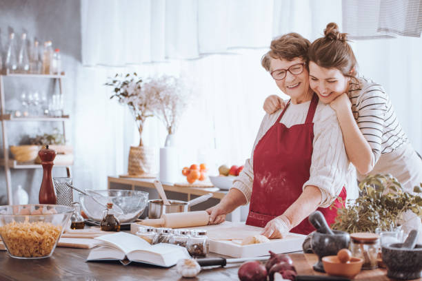 granddaughter hugging grandmother in the kitchen - family dinner stock photos and pictures