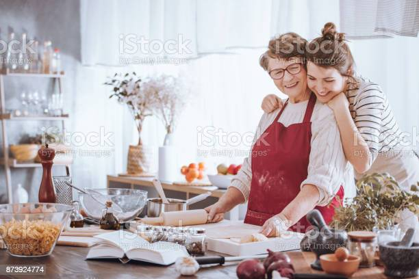 Granddaughter hugging grandmother while making cake together in the kitchen