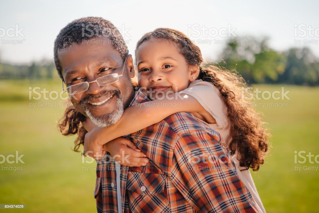 granddaughter hugging her smiling grandfather on green lawn stock photo