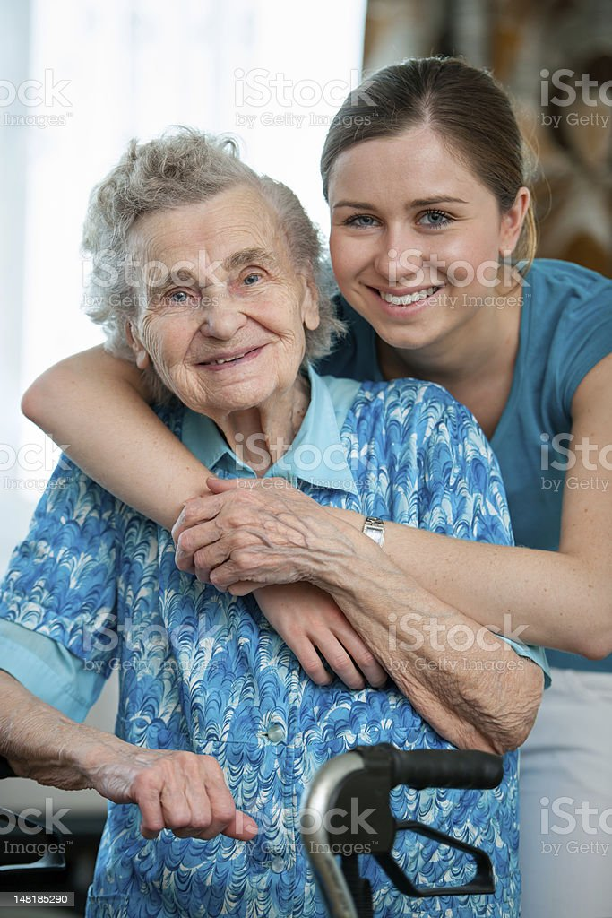 Granddaughter hugs grandmother from behind royalty-free stock photo
