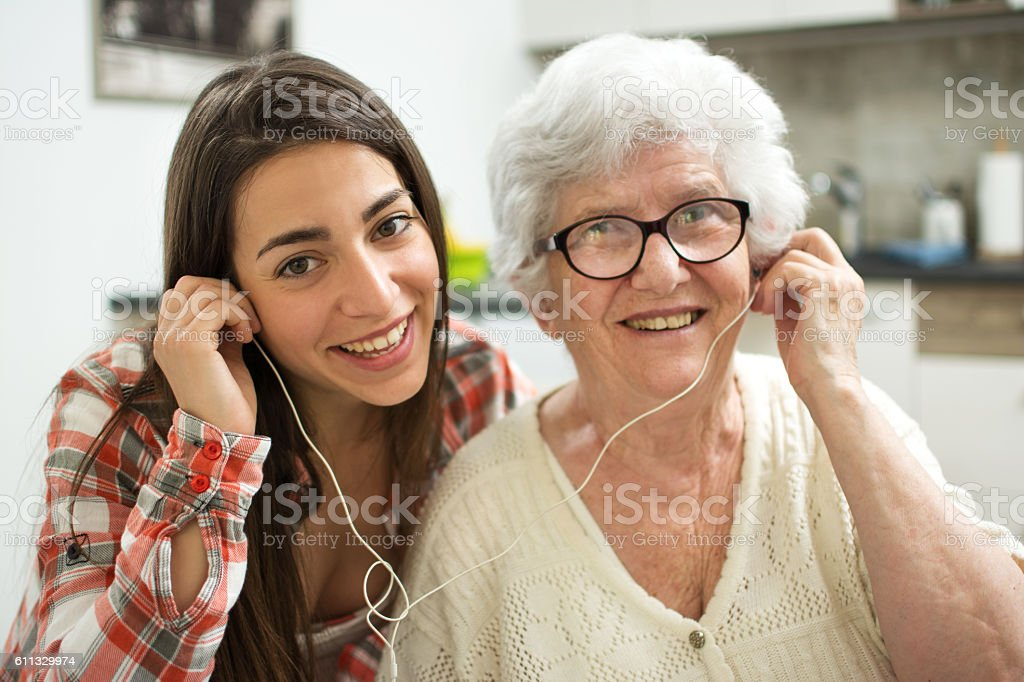 Granddaughter listening music with her grandmother at home. stock photo