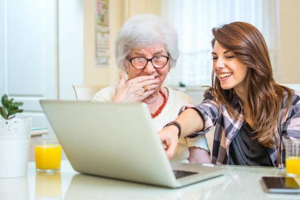Enkelin zeigt auf etwas auf Laptop-Bildschirm zu ihrer Oma zu Hause. – Foto