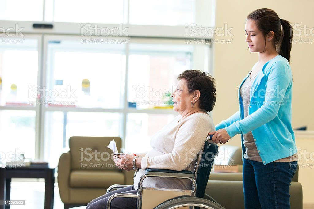 Hispanic senior woman is being pushed in a wheelchair by her...