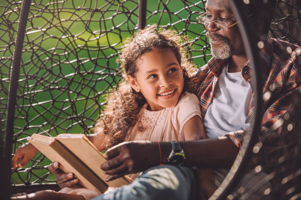granddaughter reading book while sitting in swinging hanging chair with grandfather stock photo
