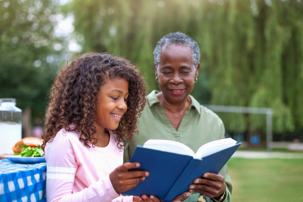 Granddaughter reading book with grandmother at public park picnic stock photo