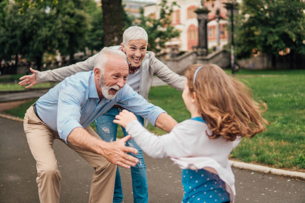 Granddaughter running into arms of her grandparents Senior couple spreading their arms for the child running towards them granddaughter stock pictures, royalty-free photos & images