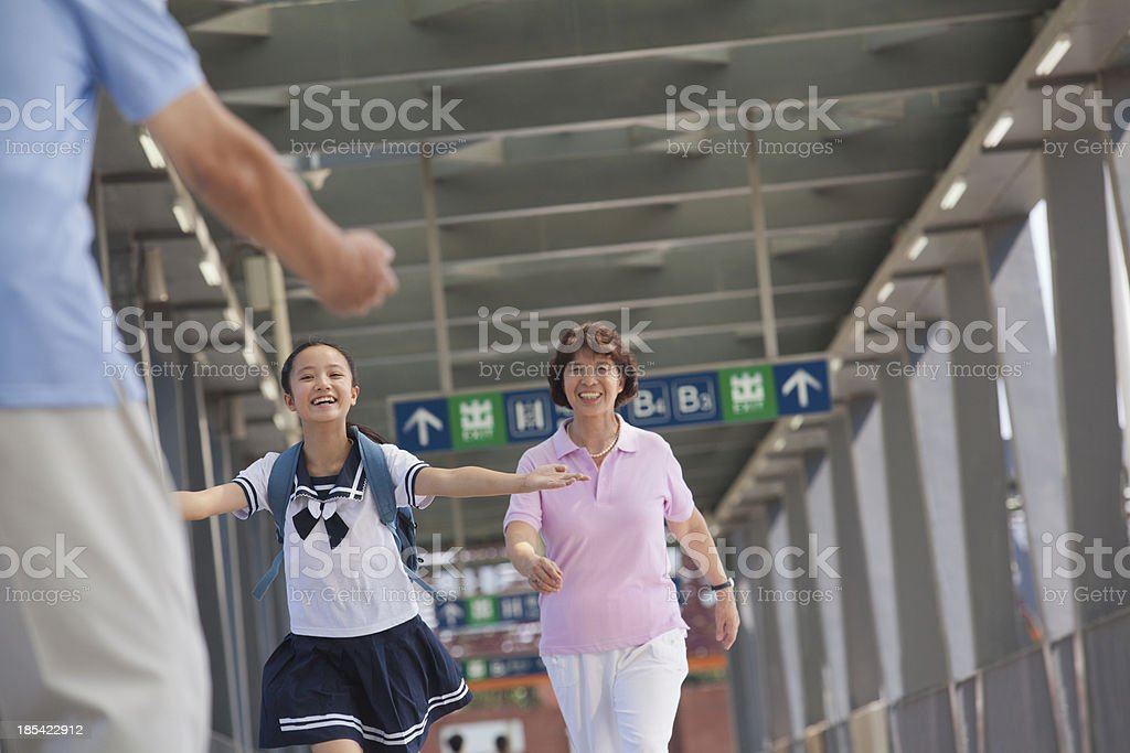Granddaughter running towards her grandfather royalty-free stock photo