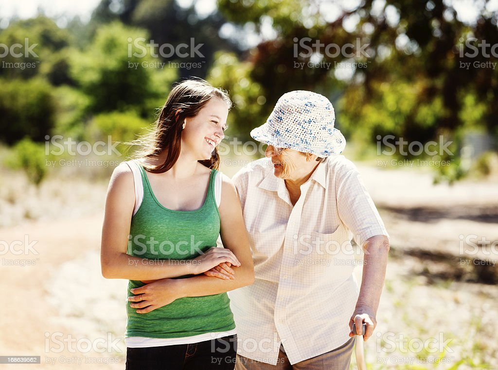 Granddaughter smilingly helps aged grandmother on forest walk royalty-free stock photo