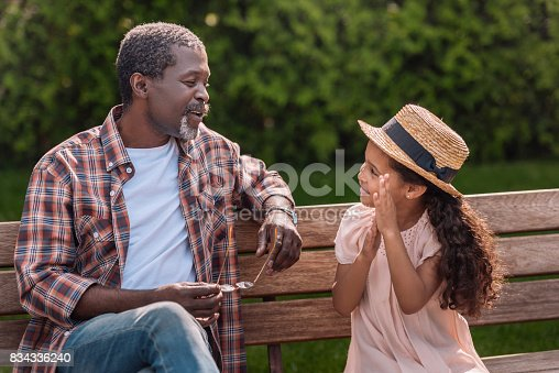 istock granddaughter talking with her grandfather sitting on bench in park 834336240