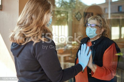 Granddaughter visiting grandmother on her 70s wearing a protective face mask standing indoors at home and touching window with hand  to her granddaughter outdoors in times of COVID-19, granddaughter is wearing mask and gloves.