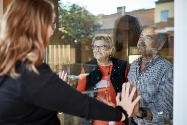 Granddaughter visiting grandparents during pandemic stock photo
