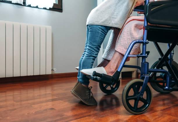 enkelin besucht ihre großmutter im rollstuhl - granny legs stock-fotos und bilder