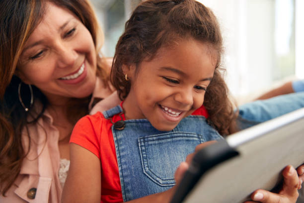 Granddaughter With Grandmother Sitting On Sofa At Home Using Digital Tablet stock photo
