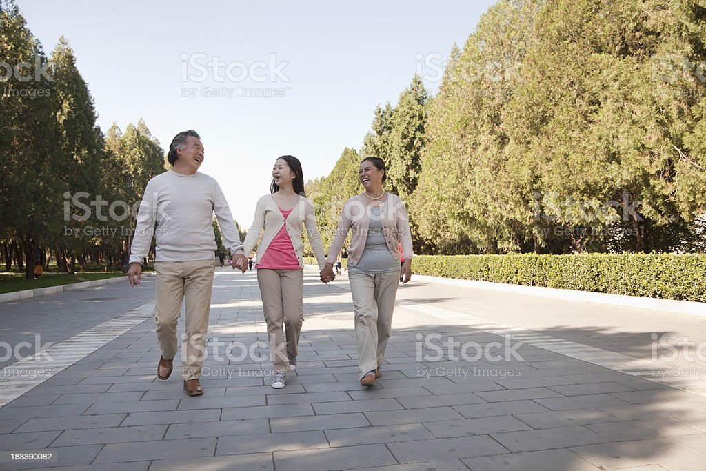 Granddaughter with grandparents walking in the park royalty-free stock photo