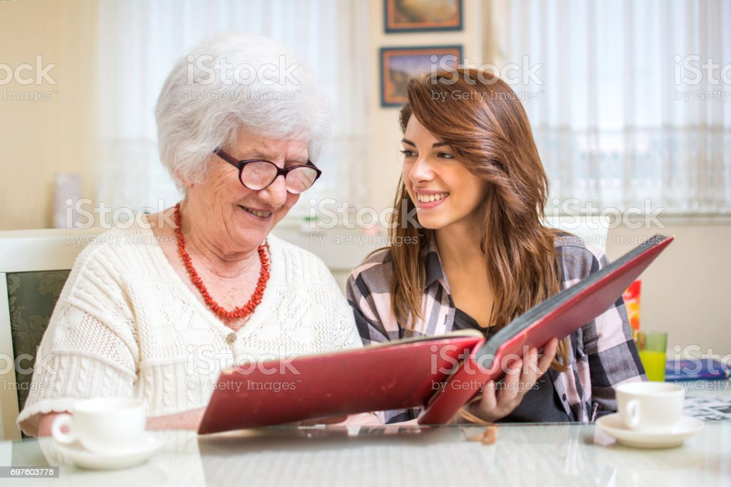 Granddaughter with her grandmother looking at photo album. stock photo