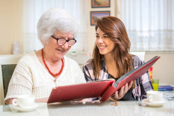 Granddaughter with her grandmother looking at photo album. - foto stock