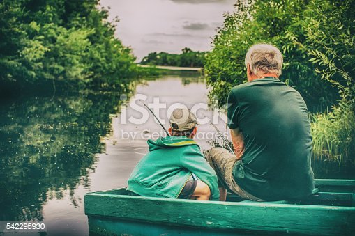 HDR. boy and an old man sitting in a boat with a fishing rod. view from the back