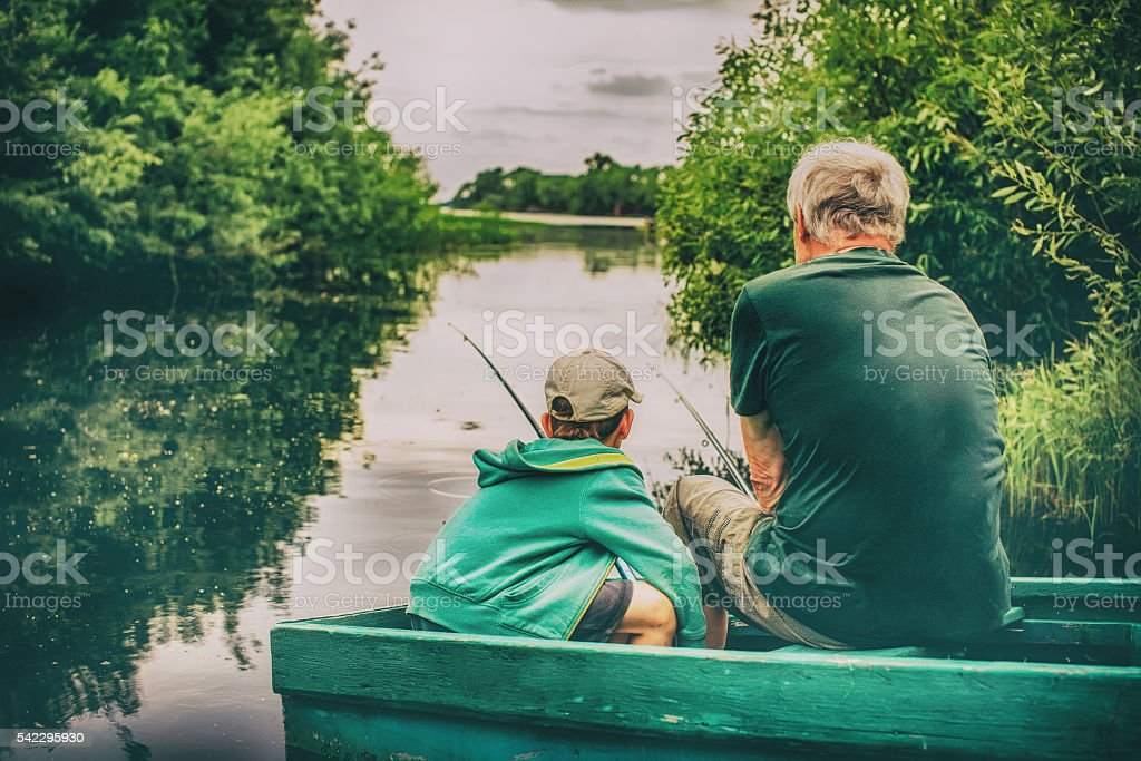 grandfather and boy fishing together stock photo