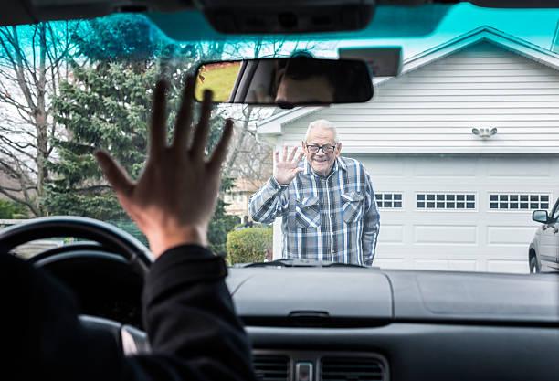 petit-fils et grand-père de pilote agitant adieu au pare-brise - homme faire coucou voiture photos et images de collection